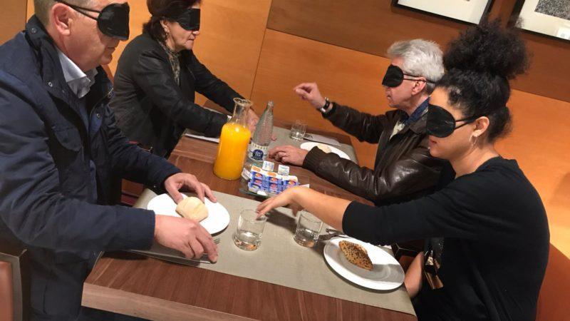 Grup de persones menjant a taula amb els ulls tapats